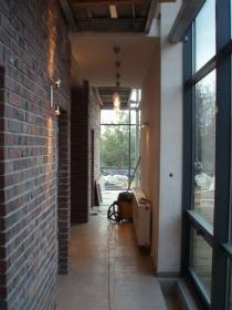 ściana ceglana jako masa termiczna przechwytująca ciepło słoneczne ze szklanej ściany osłonowej
